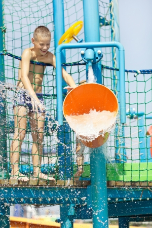 little boy having fun in aqua park with water bucket photo
