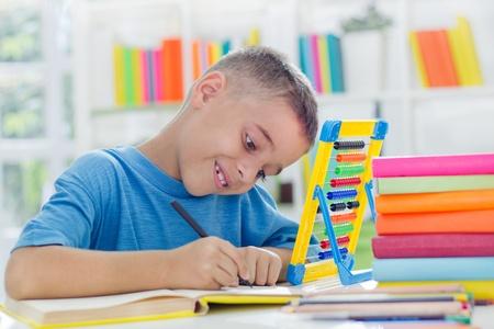 niños estudiando: sonriendo poco de estudio del niño escolar