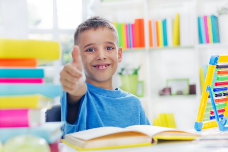 little school boy with thumb up doing homework photo