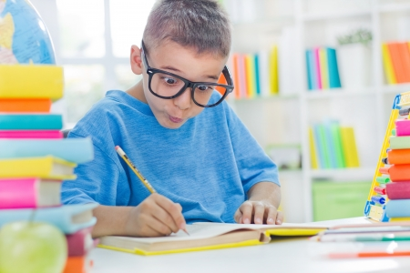 little scientist with glasses writing his homework photo
