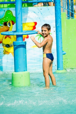 smiling boy having fun at aqua park photo