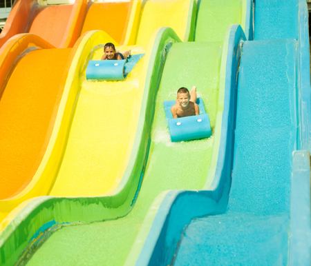 Two childs having fun in  waterslide in aquapark photo