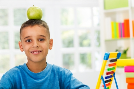 worktable: child playing with apple on worktable Stock Photo