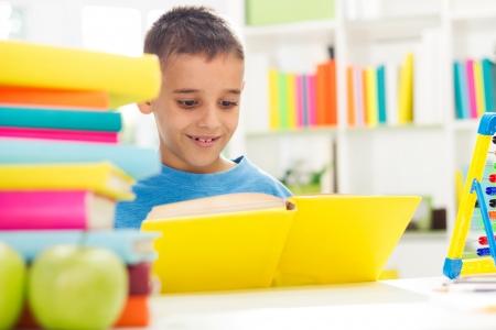 Happy smiling boy reading  photo