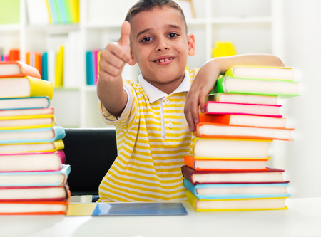 Smiling boy with pile of books photo
