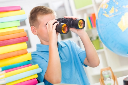 Blonde boy using binoculars while studying photo