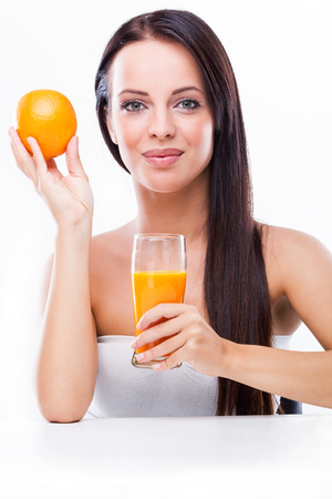 Beautiful young woman holding orange and orange juice photo