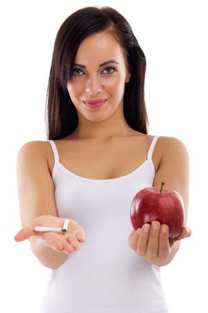 une jeune femme tenant dans une main une cigarette brisée dans l'autre cigare de pomme saine, arrêter de fumer concept sur fond blanc Banque d'images