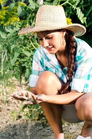 Beautiful woman planting in garden  photo