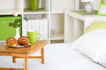 bed and breakfast: breakfast in bed with pastries on a tray  and a rose in the vase Stock Photo