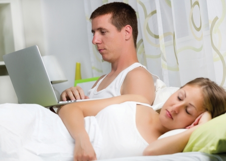 Couple with laptop in bed, Man using computer, woman sleep Stock Photo
