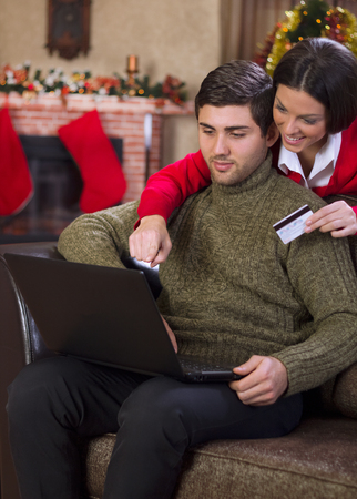young happy  Couple Using Credit Card to E-Shop on christmas night photo