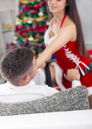 woman seduces a man in costume santa photo