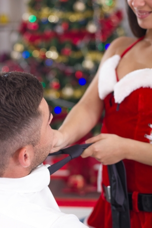 Sexy santa woman pulling tie of man  photo