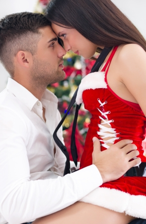 young  sexy female Santa seduces man  photo