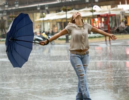 chateado: mulher de sorriso com guarda-chuva desfrutando na chuva Banco de Imagens