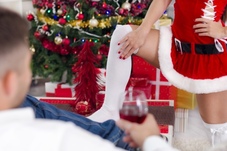 female Santa seduces man on Christmas Eve Stock Photo