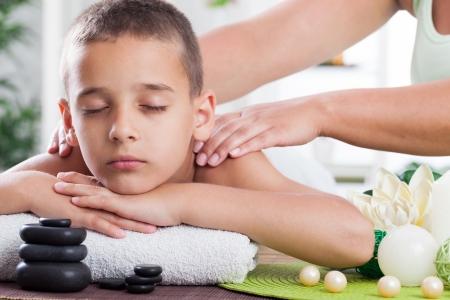 jeune garçon se détendre dans le spa. Massage aux pierres.