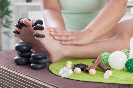 boy foot ready to spa treatment with massage stones Stock Photo