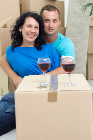 couple in their new home with cardboard boxes around photo