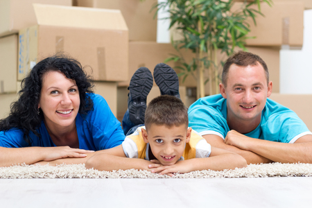 Happy couple with a kid in their new home laying on the floor photo