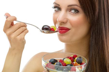 Beautiful young woman eating fresh fruit salad  photo