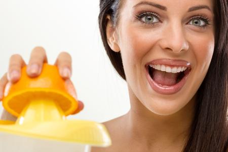 Woman squeezes an fresh orange  photo