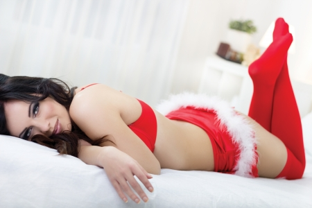 provocative young woman in red lingerie lying on the bed  Stock Photo