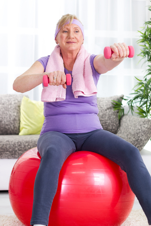 Senior woman sitting on gym ball, and exercise  photo