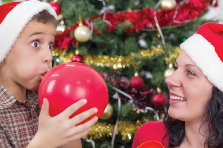 to inflate: mother helps son to inflate balloons at Christmas night