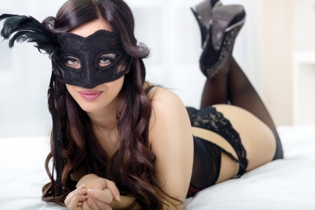 top view picture of sexy masked girl in black lingerie lying on bed photo