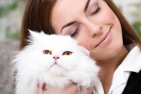 young woman holding a Persian cat  at home