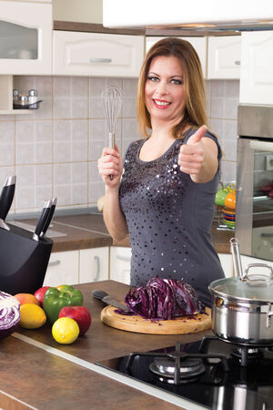 housewife prepare a meal  and shows a thumbs up photo