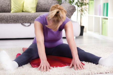 Senior woman exercising at home photo