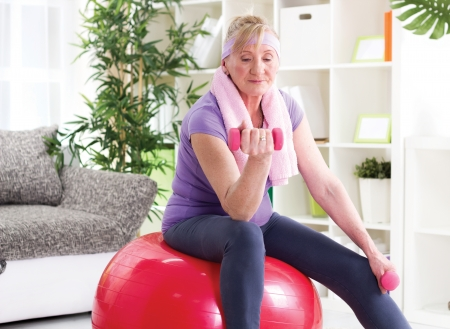 Senior woman sitting on gym ball, and exercise