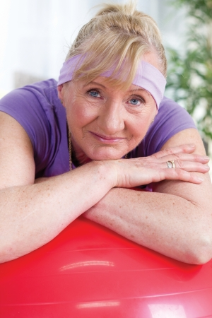 senior woman resting after exercises in red gymnastic ball photo