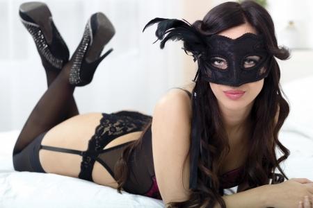 lenceria: Retrato de joven atractiva, sensual en ropa interior negro en la cama con máscara