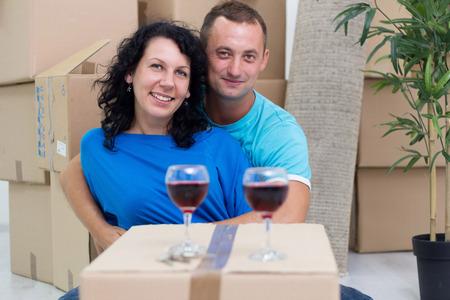 Happy couple in their new home with cardboard boxes  photo