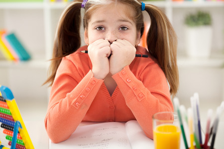 child stress: A little girl bored with her homework. Stock Photo