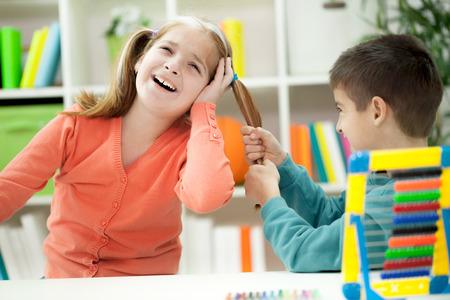niño llorando: muchacho que tira del pelo de la muchacha, coquetear Foto de archivo