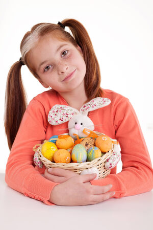 beautiful little red-haired girl with pigtails holding Easter eggs photo