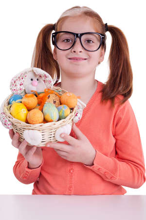 beautiful little red-haired girl with pigtails holding Easter eggs basket photo