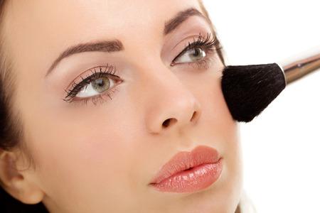 mujer maquillandose: Mujer que aplica maquillaje cepillo cosm�ticos en el fondo blanco de maquillaje. Foto de archivo
