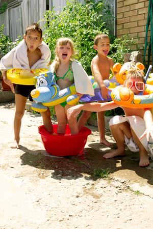 quatre petits enfants éclaboussures et s'amuser dans leur cour, jeu d'été