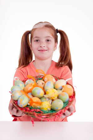 girl with pigtails holding a basket of Easter eggs photo