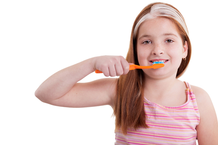 young redhaired girl brushing teeth photo