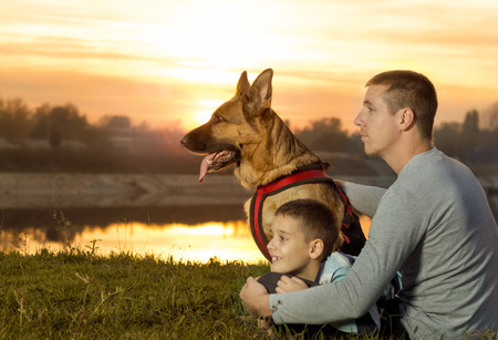 man,child, dog,in nature watching  sunset photo