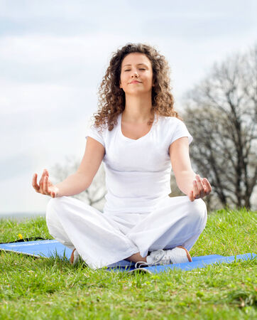 Attractive young woman in a lotus position photo