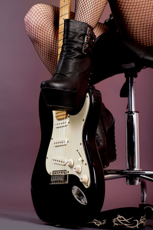 glam rock: sexy female legs in fishnet stockings and guitar Stock Photo