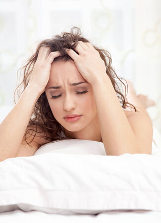 unhappy young woman lying in a bed and gets a headache photo